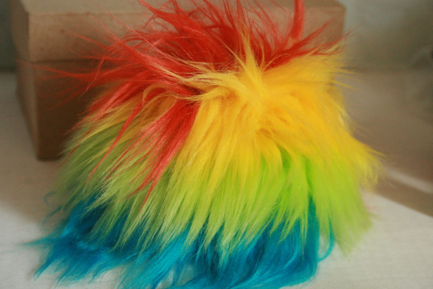 Fur wig in almost a rainbow of colors. This is a 6-7inch wig and thus too small for anyone in my small populations. However, I hope to enlarge it somehow to, first, fit a 7-8inch head and, second, include some red in its spectrum.