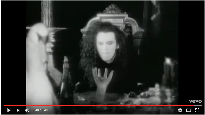"""...But you're not there!"" Ooops, he's gone off the deep end and started yelling at the disembodied hands. These appear throughout the video, holding chandeliers, reaching through the table, and caressing the meat [really -- see later screenshot!]. Not sure what they refer to [the Thing in the Addams Family?], but they provide a great way to enhance the uncanniness of the otherwise pretty cheap set."